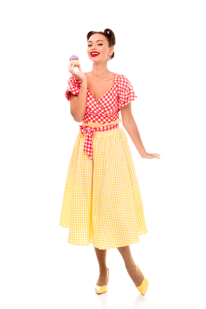 Pin up woman holding cupcace with purple cream while standing on high heels