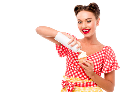 Beautiful pin up girl applying whipped cream on cupcake and looking at camera isolated on white