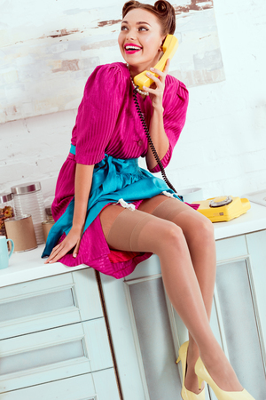 smiling pin up girl sitting on kitchen table and talking on vintage yellow phone