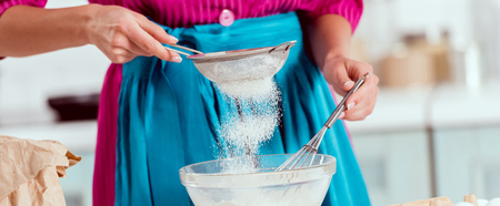 Cropped view of woman girl in blue apron sifting flour