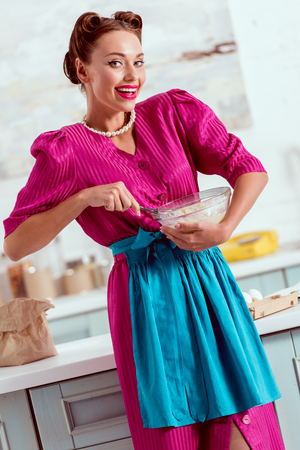 Smiling pin up girl in crimson dress and blue apron mixing ingredients for dough Stock Photo