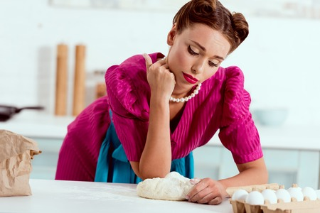 tired pin up girl with flour leaning on kitchen table Stock Photo