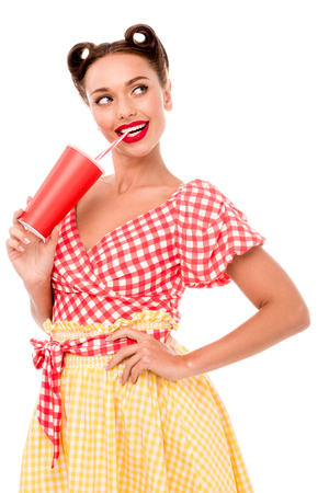 Smiling pin up girl drinking from paper cup with straw and keeping hand on hip isolated on white