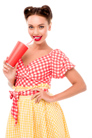 Smiling pin up girl drinking from paper cup with straw isolated on white