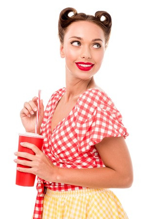Beautiful smiling pin up girl holding red disposablel cup isolated on white