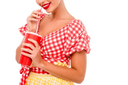 Partial view of pin up girl drinking from red disposal cup with straw isolated on white
