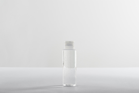 Cosmetic bottle with transparent liquid on white background with copy space