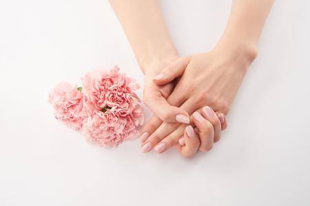 Częściowy widok kobiecych dłoni i kwiatów goździków na białym tle Zdjęcie Seryjne