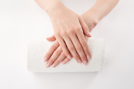 Partial view of female hands on terry rolled towel on white background Stock Photo
