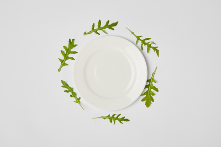 top view of empty plate surrounded by green leaves on grey background Imagens - 116392279