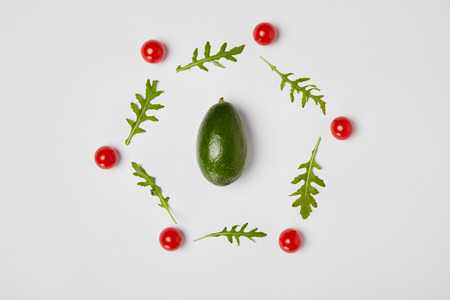 top view of avocado, arugulas leaves and cherry tomatoes on grey background