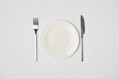top view of porcelain plate with fork and knive on grey background