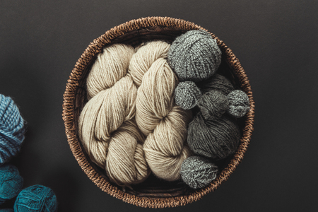 top view of beige and grey knitting clews in wicker basket on grey backdrop with blue yarn
