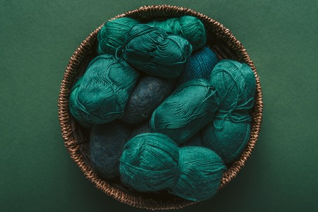 top view of green and blue yarn clews in wicker basket on green backdrop
