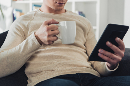 cropped view of man holding ebook and cup of coffee at home 免版税图像