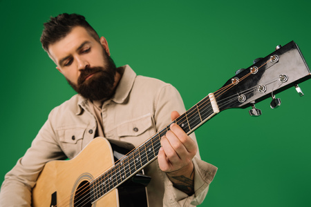 handsome man playing on acoustic guitar, isolated on green Reklamní fotografie