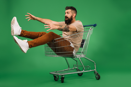 excited man gesturing and sitting in shopping cart isolated on green