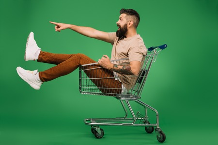 excited bearded man showing something while sitting in shopping cart isolated on green