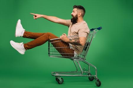 aufgeregter bärtiger Mann, der etwas zeigt, während er im Einkaufswagen sitzt, isoliert auf Grün