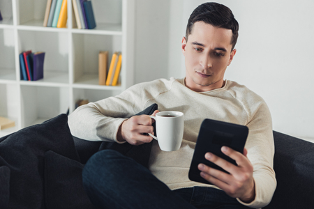 focused man studing with e-book while sitting on sofa at home Stok Fotoğraf