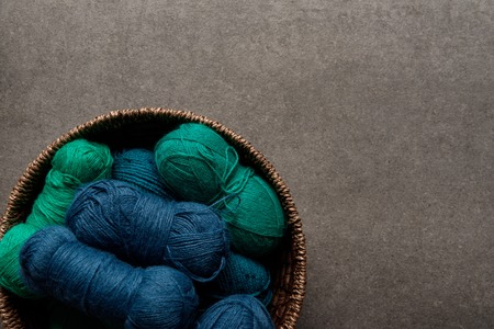 top view of green and blue yarn clews in wicker basket on grey background Stock fotó