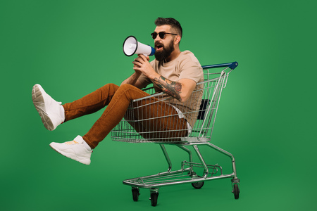 bearded man with megaphone sitting in shopping cart isolated on green