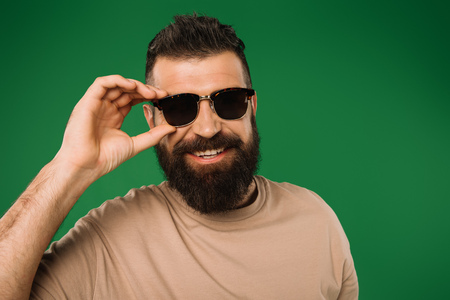 smiling bearded man in sunglasses, isolated on green