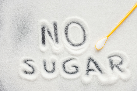 top view of no sugar lettering written on granulated sugar with plastic spoon