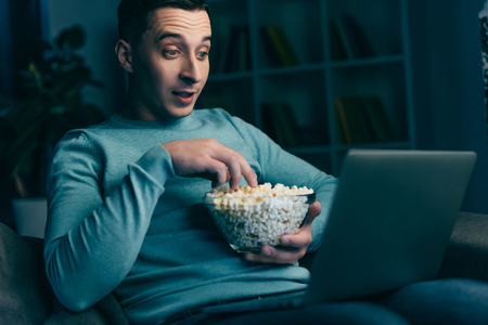 surprised man watching movie on laptop and holding bowl with popcorn at home