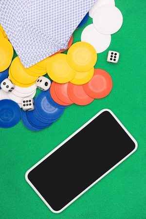 top view of green poker table with multicolored chips, playing cards, dices and smartphone