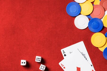 top view of red poker table and multicolored chips, dices and cards