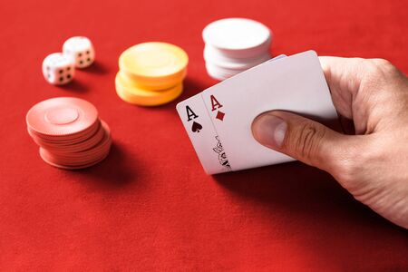 selective focus of man holding playing cards with chips and dices on background