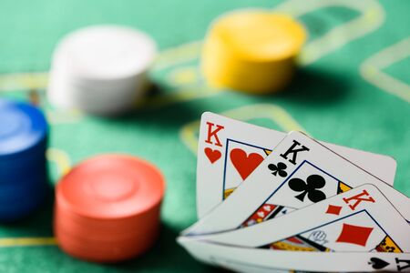 selective focus of playing cards with chips and green poker table on background