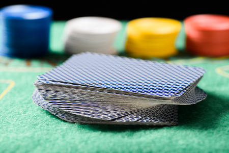 selective focus of playing cards in deck on green poker table with chips on background