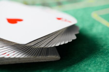 selective focus of playing cards in deck on green poker table