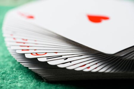 selective focus of unfolded playing cards on green table