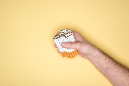 Partial view of man holding cigarettes in fist isolated on yellow Stock Photo