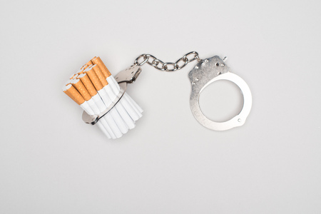 Studio shot of handcuffs and cigarettes isolated on grey, nicotine addiction concept