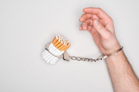 Vista parziale dell'uomo in manette in posa con sigarette isolate su grigio, concetto di dipendenza da nicotina