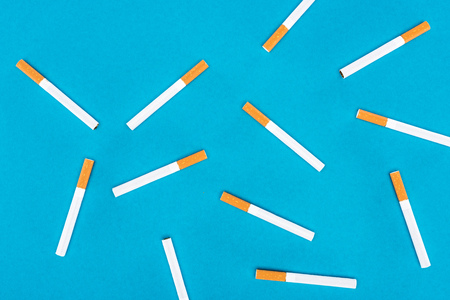 Flat lay of cigarettes isolated on blue