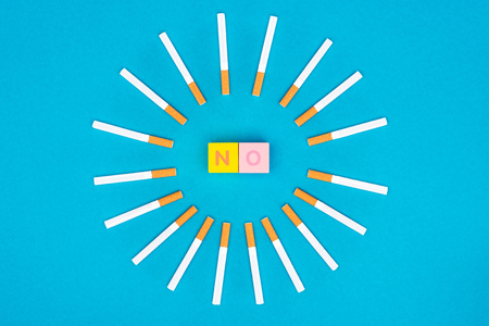 Flat lay with colorful letter cubes and cigarettes isolated on blue, stop smoking concept Фото со стока