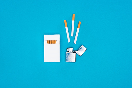 Top view of white cigarette pack and cigarette lighter isolated on blue Stock Photo