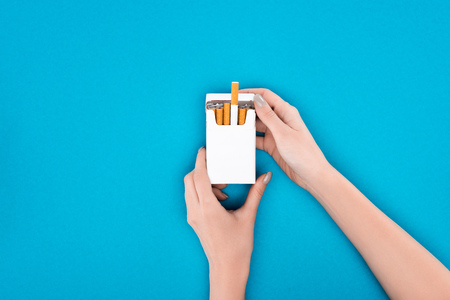 Partial shot of woman holding pack of cigarettes isolated on blue