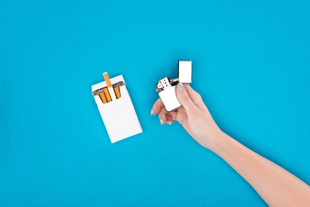 Partial view of woman holding cigarette lighter in hand isolated on blue