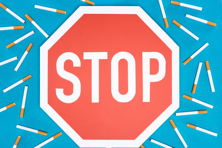 Studio shot of big stop sign with cigarettes isolated on blue, stop smoking concept Stock Photo