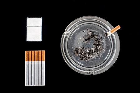 Flat lay of glass ashtray, cigarette lighter and cigarettes isolated on black