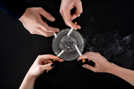 Top view of smoking people holding cigarettes