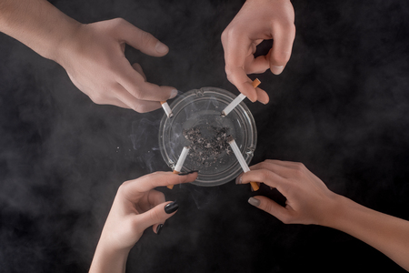 Partial view of smoking people using glass ashtray