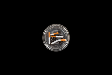 Top view of glass ashtray with ash and cigarettes isolated on black