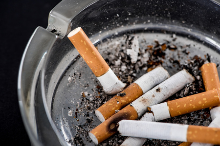 Close up shot of cigarette butts in glass ashtray Stock Photo